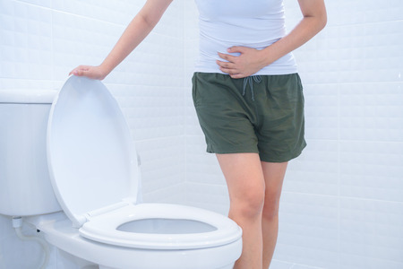A woman is sitting on toilet with diarrhea or constipated pain concept