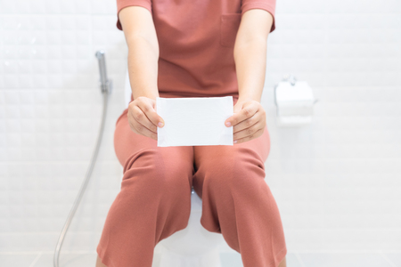 Woman holding sanitary napkins and sitting on toilet - woman on her period.