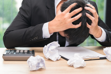 Stressed businessman make a mistake with chewed paper - migraine or headache concept.