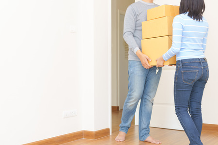 Couple holding boxes and walking together - moving house concept.Couple holding boxes and walking together - moving house concept.
