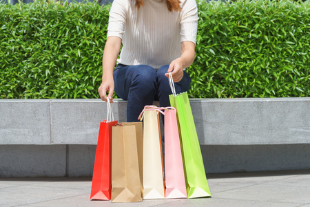 Close up of woman customer sitting and holding colorful paper shopping bags.