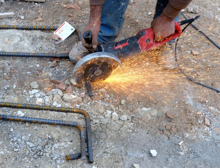 Construction worker cuts rebar circular saw on site  Standard-Bild