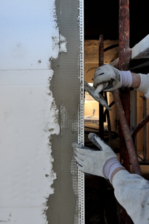 steeplejack: Construction site - Installing external insulation  Facade thermal insulation works with stopping and surfacer