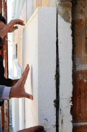 insulating: Construction site - Installing external insulation  Facade thermal insulation works with stopping and surfacer