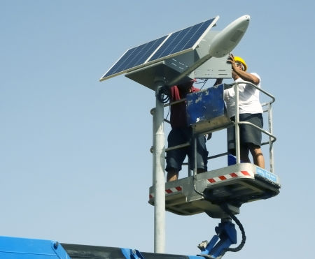 workers performing the installation of a photovoltaic kit for street lamp Standard-Bild