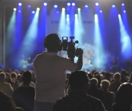soft focus: Silueta camar�grafo en un escenario para conciertos de ruido visible por valores altos de ISO, enfoque suave, DOF bajo, ligero desenfoque de movimiento Foto de archivo