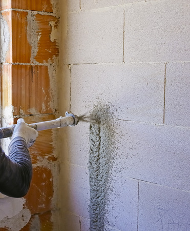 Worker performs internal plaster with machine for applying plaster