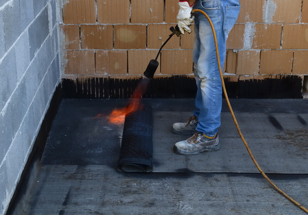 tar paper: Worker preparing part of bitumen roofing felt roll for melting by gas heater torch flame