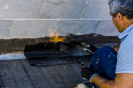 Worker preparing part of bitumen roofing felt roll for melting by gas heater torch flame photo