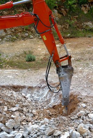smashing: Large hydraulic Jackhammer Smashing Rocks Stock Photo