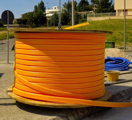 trench: Industrial cable drums of fiber optic cables from underground in a micro trench