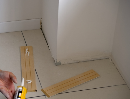 baseboard: Carpenter on work putting wood skirting board with glue. Caulking Gun in Hand. .Focus is on the tools Stock Photo