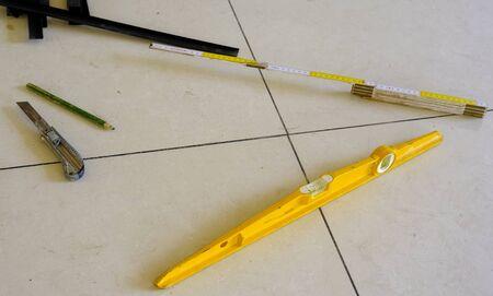 niveau, couteau, bandes, CEE. outils de travail pour un plancher flottant sur des pieds en acier.
