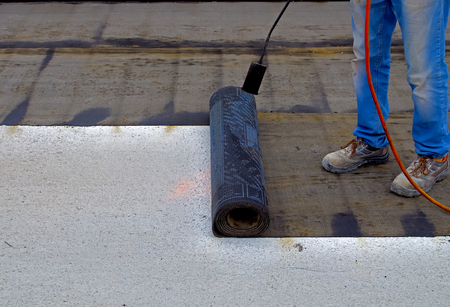 construction material: Worker preparing part of bitumen roofing felt roll for melting by gas heater torch flame