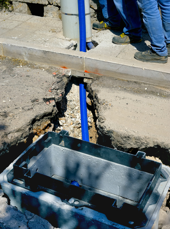 trench: fiber optic cables buried in a micro trench by a worker