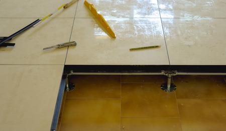 travailleur porte un plancher flottant sur des pieds en acier, en appui sur la structure d'une plaque de carreaux de porcelaine.