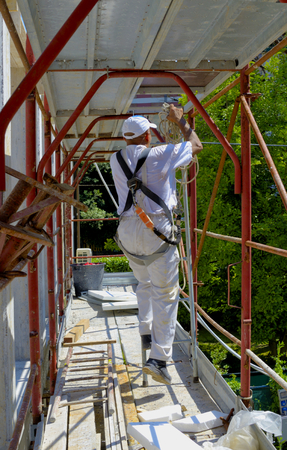 steeplejack: Safety at work. Worker assembles a scaffold