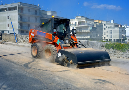 dumps: Sweeper attachments mini excavator. The sweeper sweeps, collects and dumps dirt and debris.