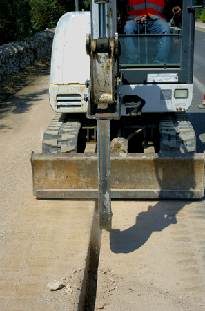 mini loader: Mini excavator dig a trench with a bucket micro very tight