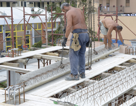 by placing: Construction workers placing the concrete beams to create a slab