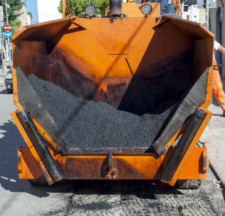 tracked: Tracked paver laying fresh asphalt during road repairing