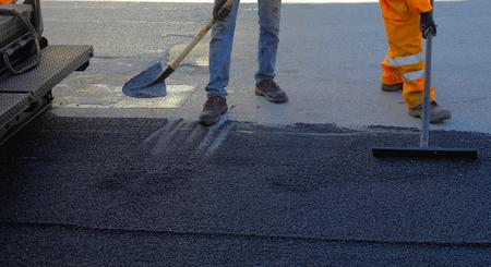 asphalting: Construction Worker  with shovel during Asphalting Road Works