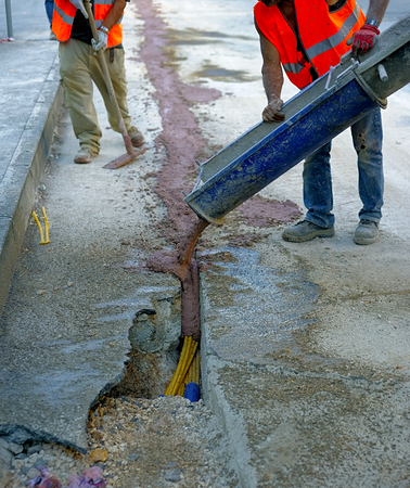 trench: fiber optic cables buried in a micro trench with concrete colored red by a worker