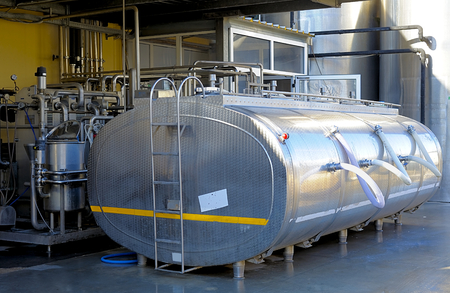 steel  milk: Large stainless steel tank containing milk located in a dairy food-processing industry