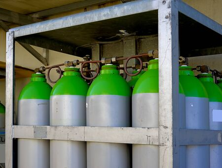 A group of industrial gas cylinders arranged in a rack on the outside of a factory