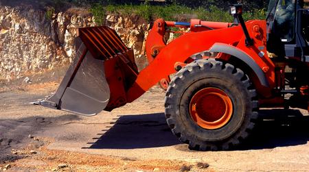 cargador frontal: delante de un gran cubo de pala cargadora sobre ruedas roja