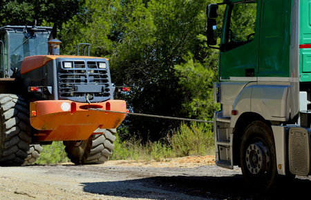 to go up: bulldozer towing truck to go up a dirt road high slope Stock Photo