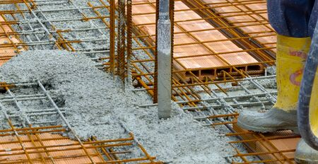 compacting: Construction worker compacting liquid cement in reinforcement form work during concreting floors pouring works Stock Photo