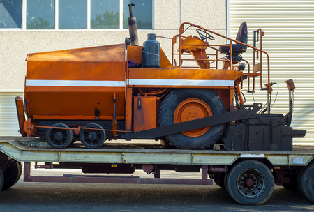 transported: A paver finisher, asphalt finisher or paving machine waiting to be transported on a road being asphalted