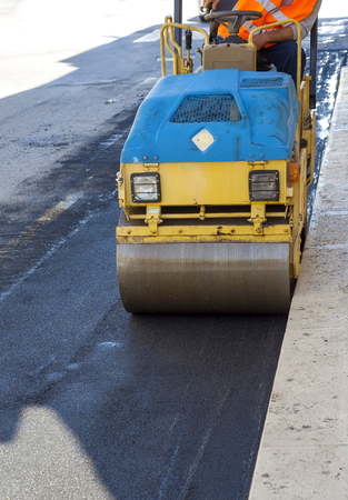 vibroroller: small tandem vibration roller compactor working on asphalt pavement Stock Photo