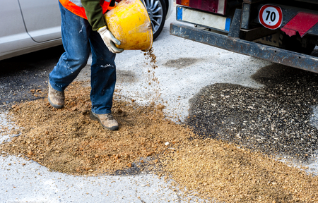 committed: worker committed to the repair of a large pit road with inert mixed stabilized. With motion blure Stock Photo