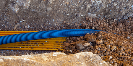 Cable duct for optical fibers and corrugated tube for underground telephone cables in a trench