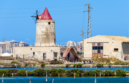 abandoned windmill in a plant for the production of sea salt (salina). Trapani, Sicily. Italy