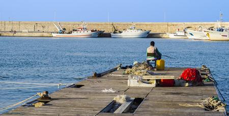 Fisherman sitting on the dock of a port Stock fotó