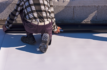 Worker on application Synthetic waterproofing PVC-P and TPO / FPO Archivio Fotografico