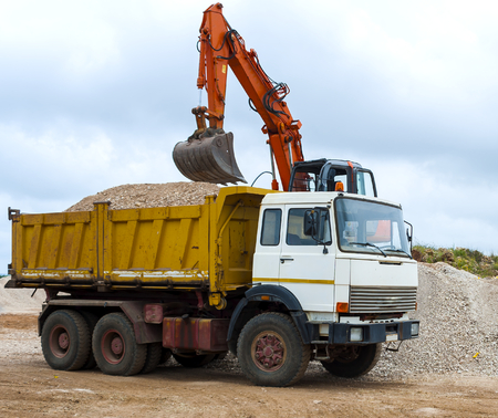 Excavator loading a truck on a construction site