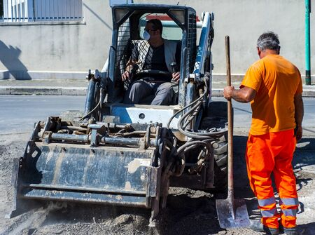 skid: Worker checks the progress of the Milling of asphalt for road reconstruction accessory for skid steer