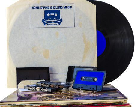 Anti-piracy advertising on the cover of an old vinyl record. A stack of old vinyl 33 rpm and some cassette tapes Stock Photo