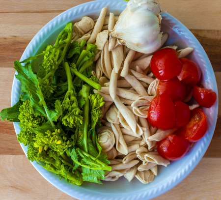A dish of ingredients for the typical flat Bari: orecchiette with turnip tops.Orecchiette, tomatoes, garlic and turnip greens Stock Photo
