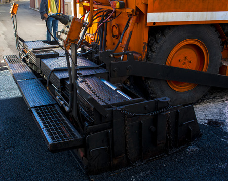 close-up details of industrial machinery working with asphalt, mixing bitumen with hot asphalt, layering on the road surface Stock Photo