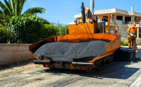industrial truck laying fresh bitumen and asphalt at road construction site Stock Photo