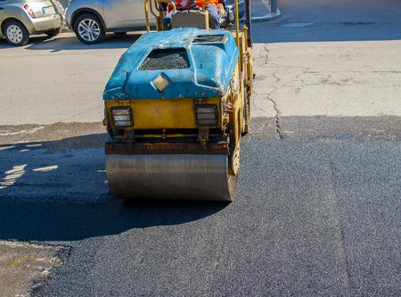 Worker on light vibration roller compactor at asphalt pavement works for road repairing