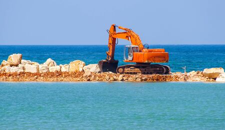 building the jetty with heavy excavator machine.Note the turbulence of the air from the exhaust pipe of the excavator Stock Photo