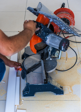 Closeup view of a man that is cutting wooden board electric circular saw. Focus is on the tools Stock Photo