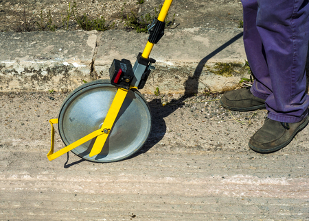 Surveyor with measuring wheel (odometer) detects the length of an excavation of minitrench.Close up odometer meter