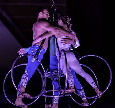 Bitonto, Italy - May 28, 2017: Acrobats perform a trick on slings suspended in the void and secured with harnesses on a festive evening in the main square of Bitonto, Puglia